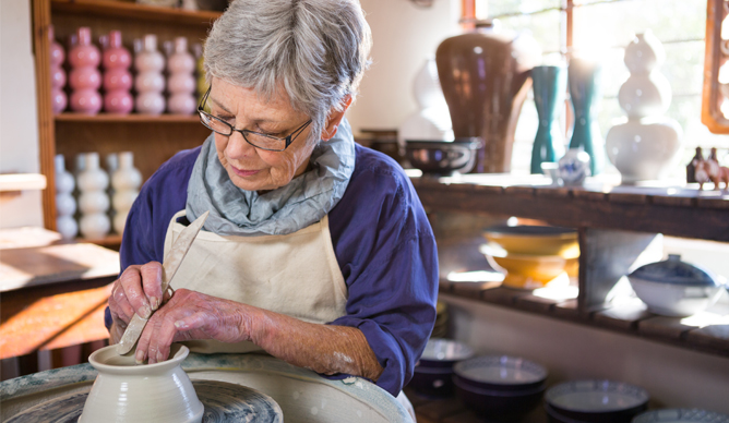 A woman busy making clay